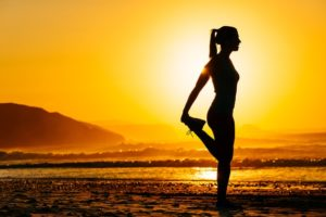 woman stretching against a sunrise